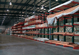 integrated racking system in multiple-aisle drive-thru buildings providing covered storage for building materials and lumber