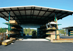 drive-thru shed with overhang and rack system for building materials storage
